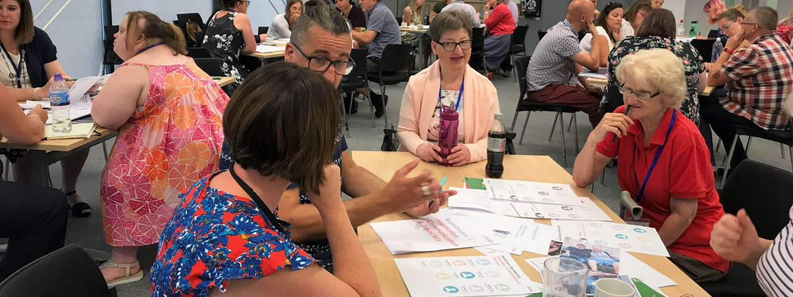 group of people round a table looking at easy read resources